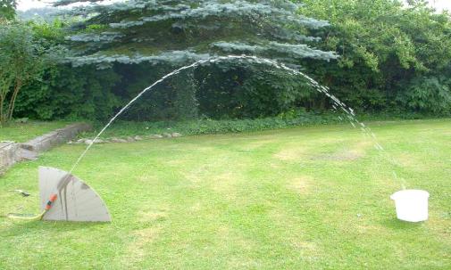 Mit einem Gartenschlauch wird ein parabelförmiger Wasserstrahl erzeugt.