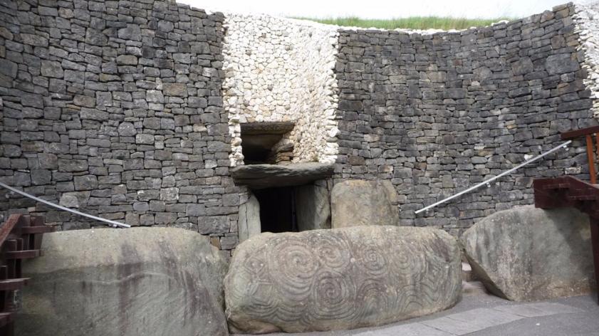De ingang tot de tombe wordt afgeschermd door grote stenen met spiralen en zigzagvormen.